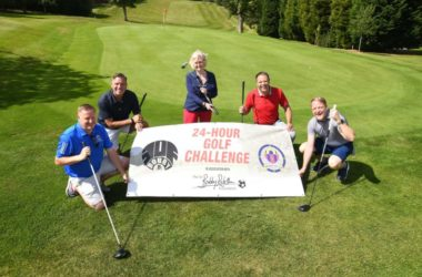 Lady Elsie and group holding 24 hour golf challenge poster on putting green.