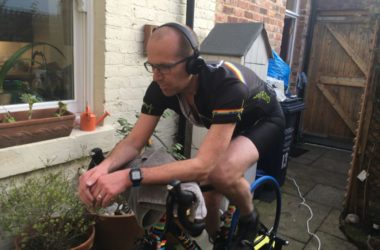 Keith Farquharson on a bike with headphones.
