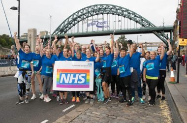 Group of people stood under the Tyne Bridge after completing the Great North Run.
