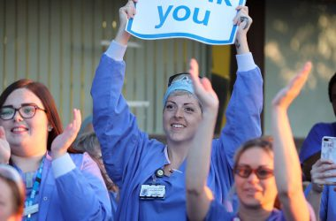 A group of nurses clapping and one is holding a thank you sign